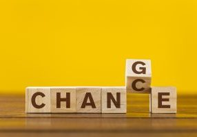 """Wooden cube with word """"Change & Chance"""" concept on yellow background"""